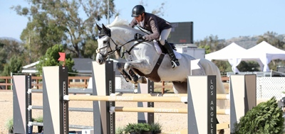 A horse is ridden over a jump in an arena with FSGeoTEX footing